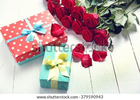 Beautiful bouquet of red roses and present boxes on wooden background - stock photo