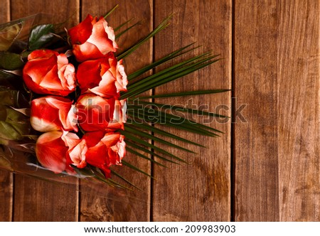 Beautiful bouquet of red roses on wooden background - stock photo