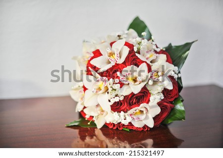 Beautiful bouquet of rose flowers, on table. Wedding bouquet of red roses. Elegant wedding bouquet on table at restaurant  - stock photo
