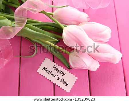 Beautiful bouquet of tulips for Mother's Day on pink wooden background - stock photo