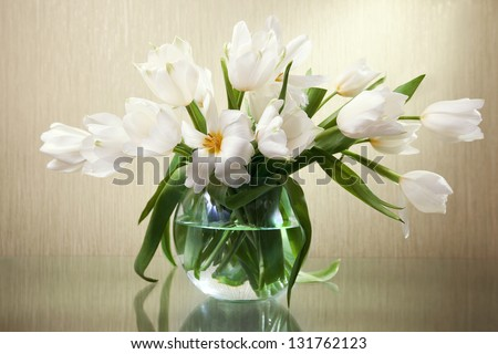 beautiful bouquet of white tulips in a vase on a glass table - stock photo