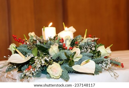 beautiful bouquet with calla lilies, white flowers and Holly on the white tablecloth - stock photo