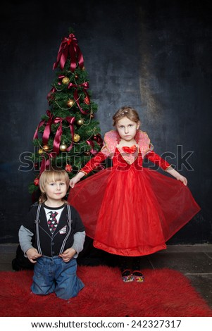Beautiful boy and girl in the photo studio on a black background in a Christmas tree in suits on the red carpet - stock photo