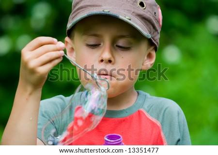 Beautiful boy blowing soap bubbles outdoors - stock photo