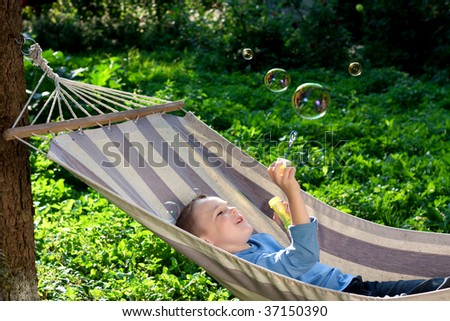 Beautiful boy blowing soap bubbles outdoors, summer - stock photo