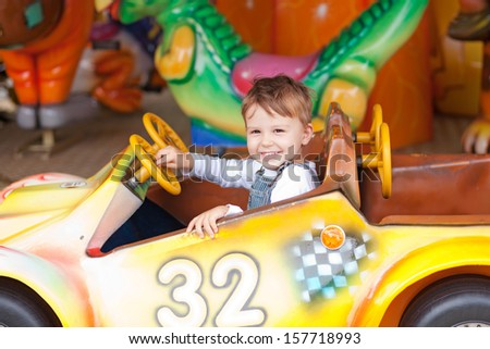 Beautiful boy having fun on the ride at the local carnival - stock photo
