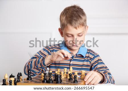 beautiful boy playing chess  - stock photo