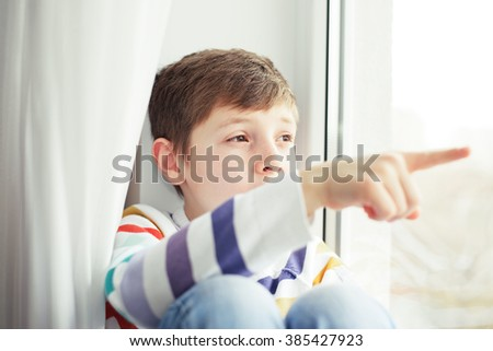 Beautiful  boy smiling and watching out the window. A child looks out the window.  Boy looking from window. Portrait of cheerful kid lies at windowsill. - stock photo