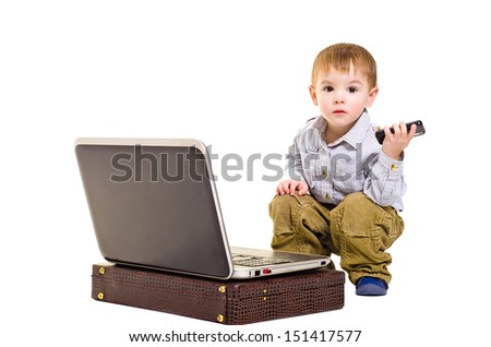 Beautiful boy with a mobile phone is sitting next to a laptop - stock photo