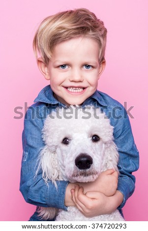 Beautiful boy with Royal Standard Poodle. Studio portrait over pink background. Concept: friendship between boy and his dog - stock photo