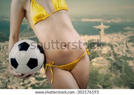 Beautiful Brazilian model wearing yellow bikini holding a soccer ball with island background - stock photo