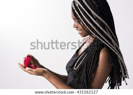 Beautiful Brazilian woman, afro descendant, with long and braided hair, receiving an engagement ring. She is happy and smiling, looking surprisingly for the ring. - stock photo
