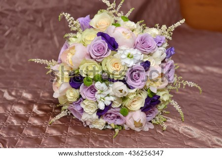 Beautiful bridal bouquet of roses lies on a satin material. Beauty of colored flowers. Bridal accessories. Details nature - stock photo