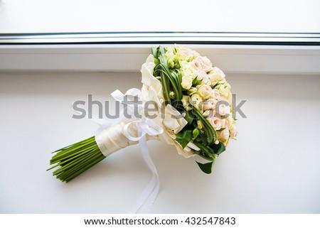 beautiful bridal bouquet of roses lying on the windowsill - stock photo