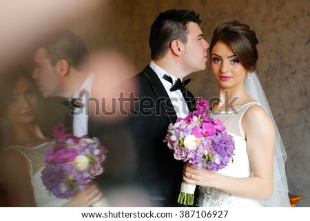 Beautiful bridal couple embracing on wedding day - stock photo
