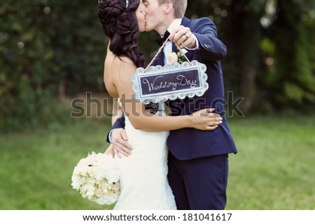 Beautiful bridal couple with Wedding Day board in their hands  - stock photo