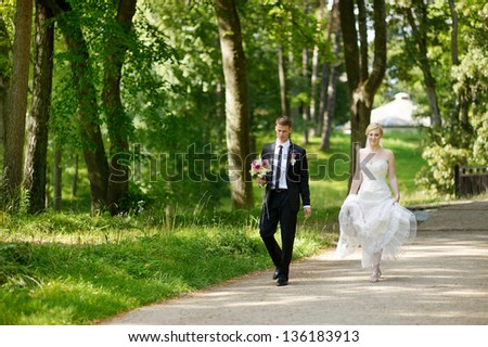 Beautiful bride and groom in a park - stock photo