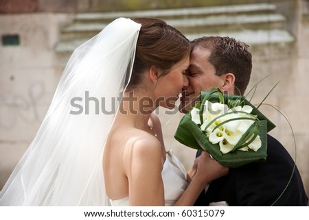 Beautiful bride and groom kissing while doing their photo shoot - stock photo