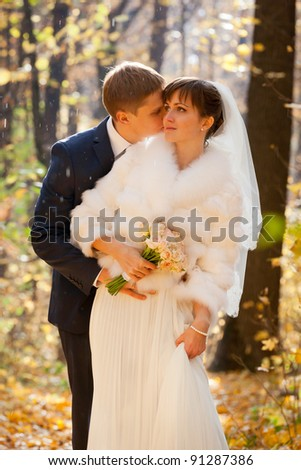 Beautiful Bride and groom together in park -rain - stock photo