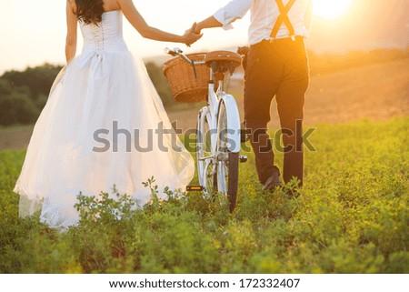 Beautiful bride and groom wedding portrait with white bike - stock photo