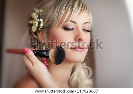 beautiful bride blond in white wedding dress with hairstyle and bright makeup. Happy sexy girl waiting for groom. Romantic lady in bridal dress and flowers in hair have final preparation for wedding - stock photo