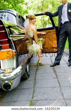 Beautiful bride coming out black luxury car - stock photo