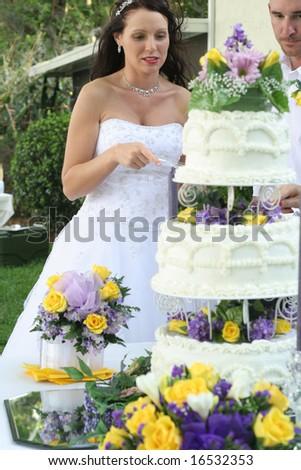 beautiful bride cutting cake - stock photo