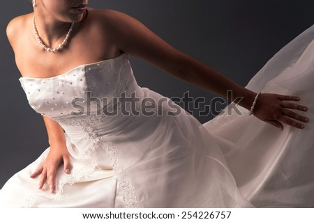 Beautiful bride detail against a gray background - stock photo