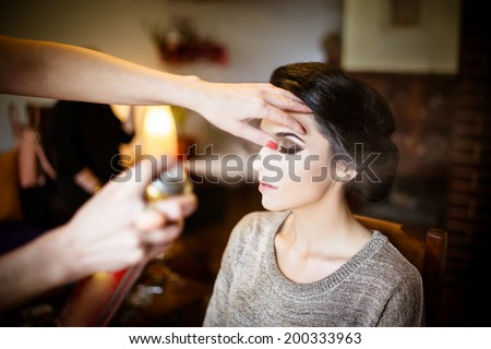 Beautiful bride doing her hair and makeup. Hairstylist spraying hairspray on her updo - stock photo