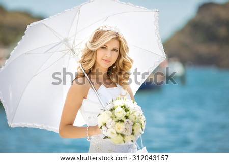 Beautiful bride girl in wedding dress with white umbrella and bouquet of flowers, outdoors portrait - stock photo