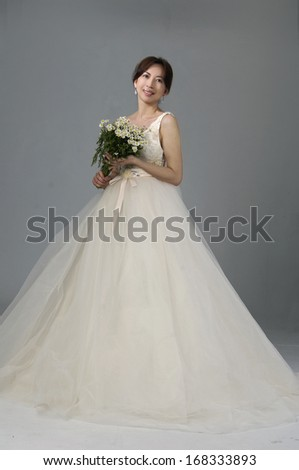 beautiful bride girl in white wedding dress on gray background - stock photo
