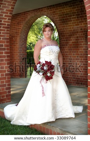 Beautiful bride holding her bouquet outside surrounded by arches on a sidewalk with a soft focus to add to the elegance. - stock photo
