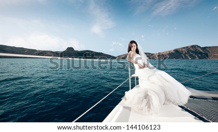 beautiful bride in a long white dress poses on a yacht at sea - stock photo