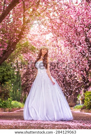 Beautiful bride in a white dress under the sakura tree and flower petals - stock photo
