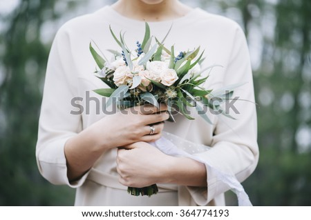 Beautiful bride in a white wedding dress holding her wedding bouquet in the forest - stock photo