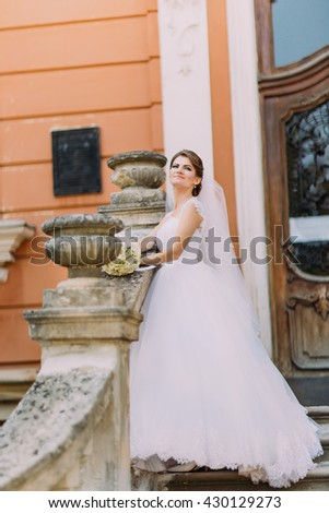 Beautiful bride in elegant white dress with long tail posing stairs romantic vintage building near baluster - stock photo