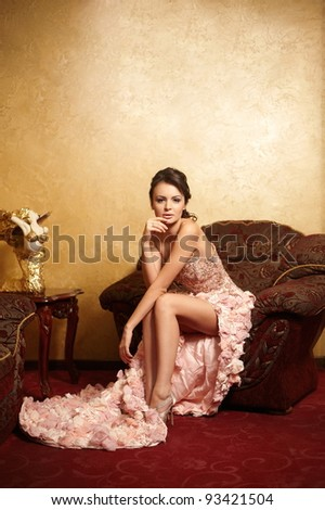 Beautiful bride in unusual wedding dress in the interior sitting in armchair - stock photo