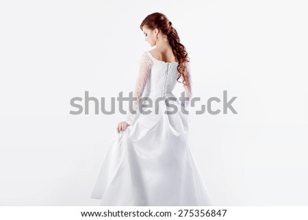 Beautiful bride in wedding dress, back, white background - stock photo