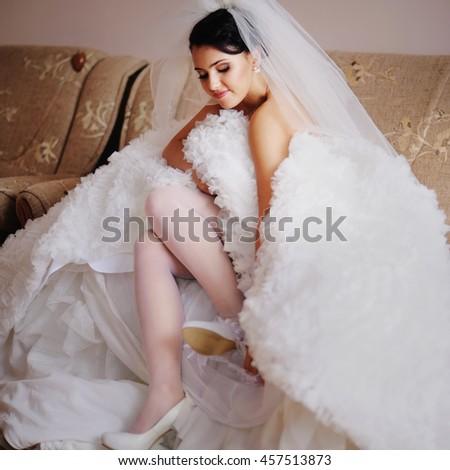 Beautiful bride in wedding dress getting ready for wedding - stock photo