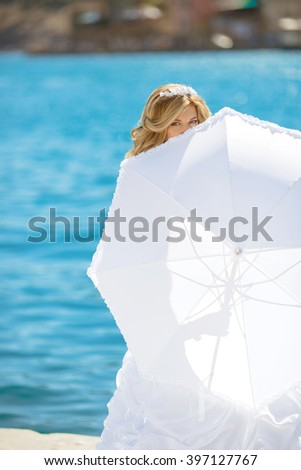 Beautiful bride in wedding dress hidden by white umbrella posing over seafront, outdoor bridal portrait. Happy smiling fun young woman.  - stock photo