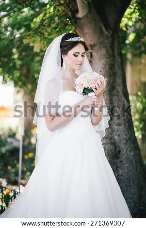 Beautiful bride in wedding dress posing in a park on her wedding day - stock photo