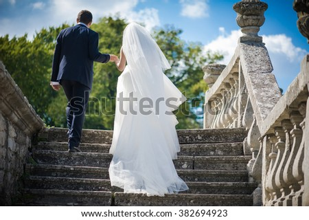 Beautiful bride in wedding dress preparing to ceremony in church. Walking near old castle - stock photo