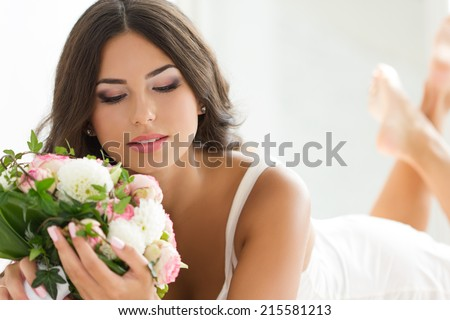Beautiful bride in white lingerie holding nuptial bouquet - stock photo