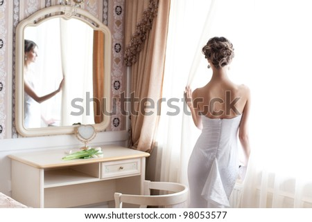 Beautiful bride in white wedding dress standing in her bedroom near the window - stock photo