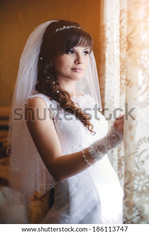 beautiful bride in white wedding dress with hairstyle and bright makeup. Happy sexy girl waiting for groom near the window. Romantic lady in bridal dress have final preparation for wedding - stock photo