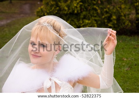 Beautiful bride is raising wedding veil. Newlywed is looking at the camera in outside. - stock photo