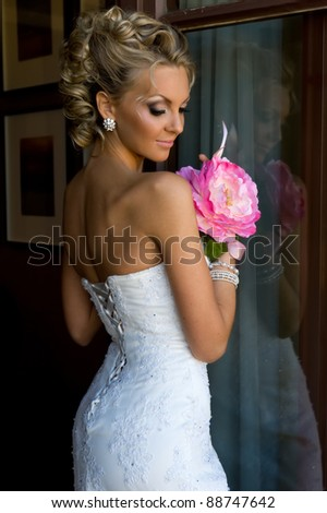 Beautiful bride is standing at the window with bunch of flowers. - stock photo
