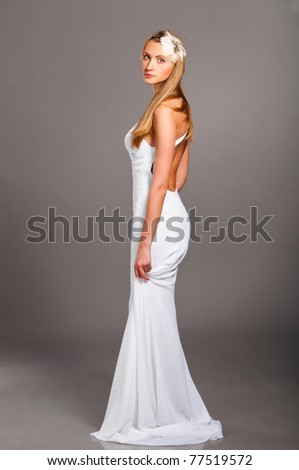 beautiful bride is standing in wedding dress on grey background - stock photo