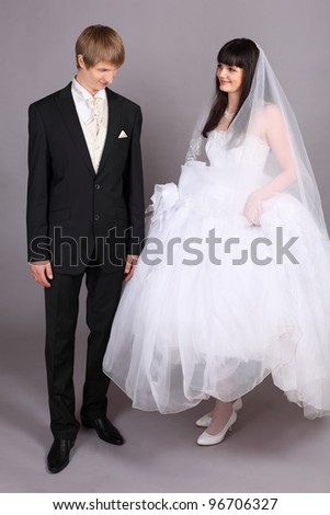 Beautiful bride lifted her dress and groom looks at her feet in studio on gray background - stock photo
