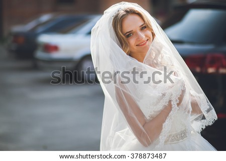 Beautiful bride near the car - stock photo